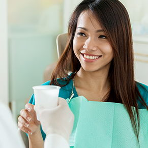 A dental patient smiling and taking a cup of water