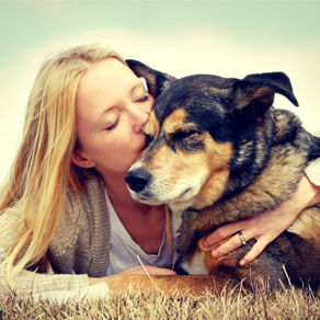 A woman hugs and kisses her dog