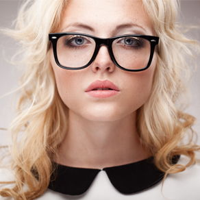 A head shot of a female model wearing large framed glasses