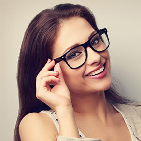 A woman smiling and touching the temple of her glasses with one hand