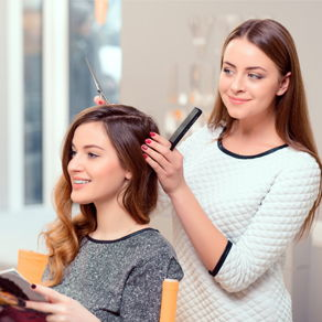 A stylist preparing to cut a young woman's hair