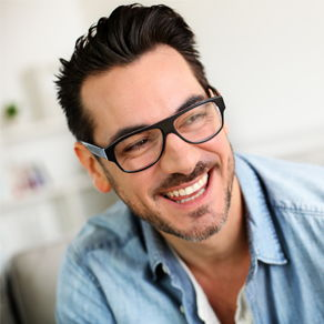 A man with glasses dressed in a jeans jacket smiling