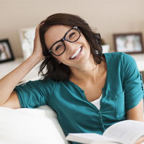 A woman wearing glasses holding an open book while sitting on a sofa and smiling