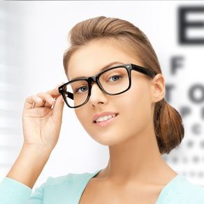 A head shot of young woman with glasses posing against the background of a Snellen chart