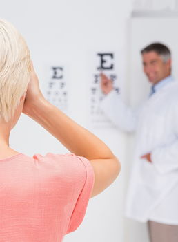 Image of a female facing an eye chart while a doctor stands in the distance