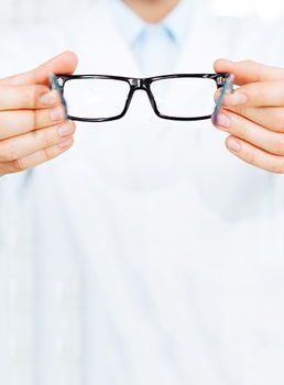 Image of a pair of hands holding out a pair of eyeglasses