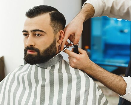 Image of a male client sitting in a barber chair having beard trimmed