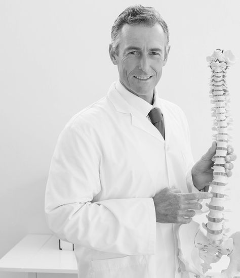 Chiropractor pointing to spine model
