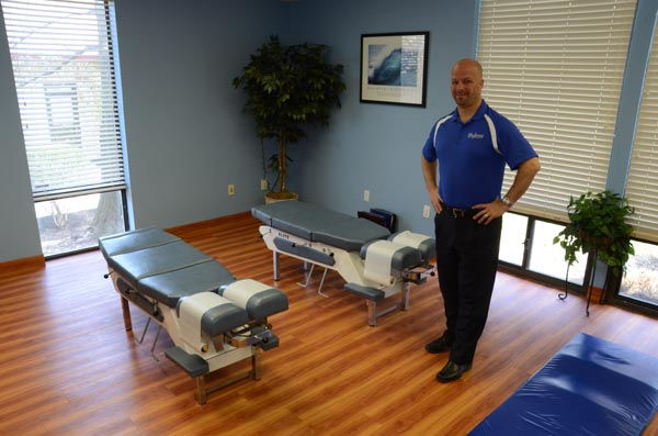 Dr. Madorno standing proudly near two adjustment tables