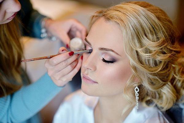 A makeup artist applies makeup to woman's face