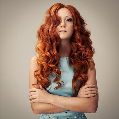 A young woman with long wavy red hair