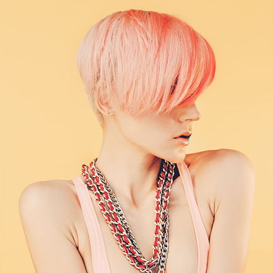 A female model with pink hair and beads on her neck